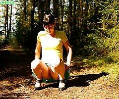 Cute brunette squats down to take a leak in forest