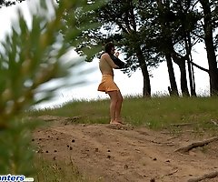 Naughty brunette pisses into a sandpit in forest