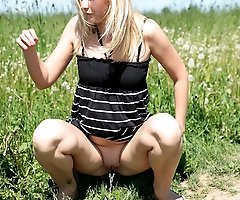 Young fair-haired hottie making water on a field