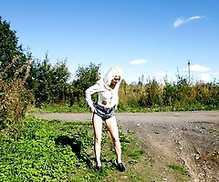 Blonde cutie tinkles on the shoulder of country road