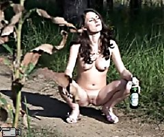 Naked brunette with perky titties pisses in forest