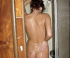 Creeping up on a naked showering brunette